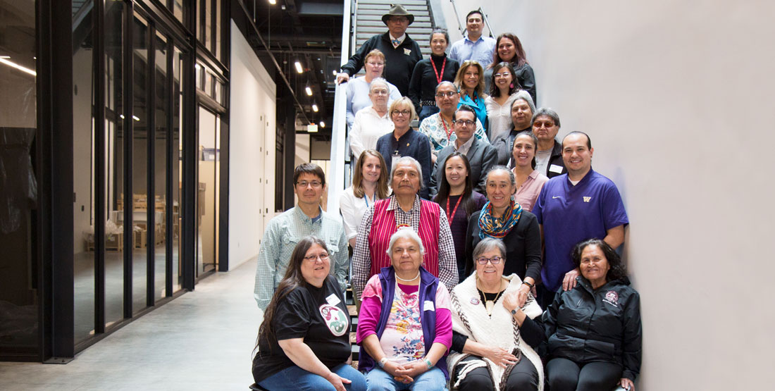 a group of people pose for a photograph on the stairs of the new burke museum