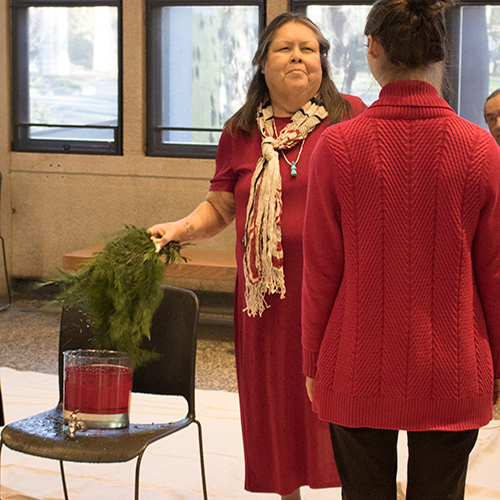 Tribal Elder dips cedar branches in water while greeting a staff member