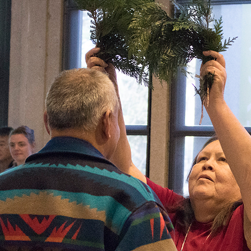 Tribal Elder receives cedar brushing