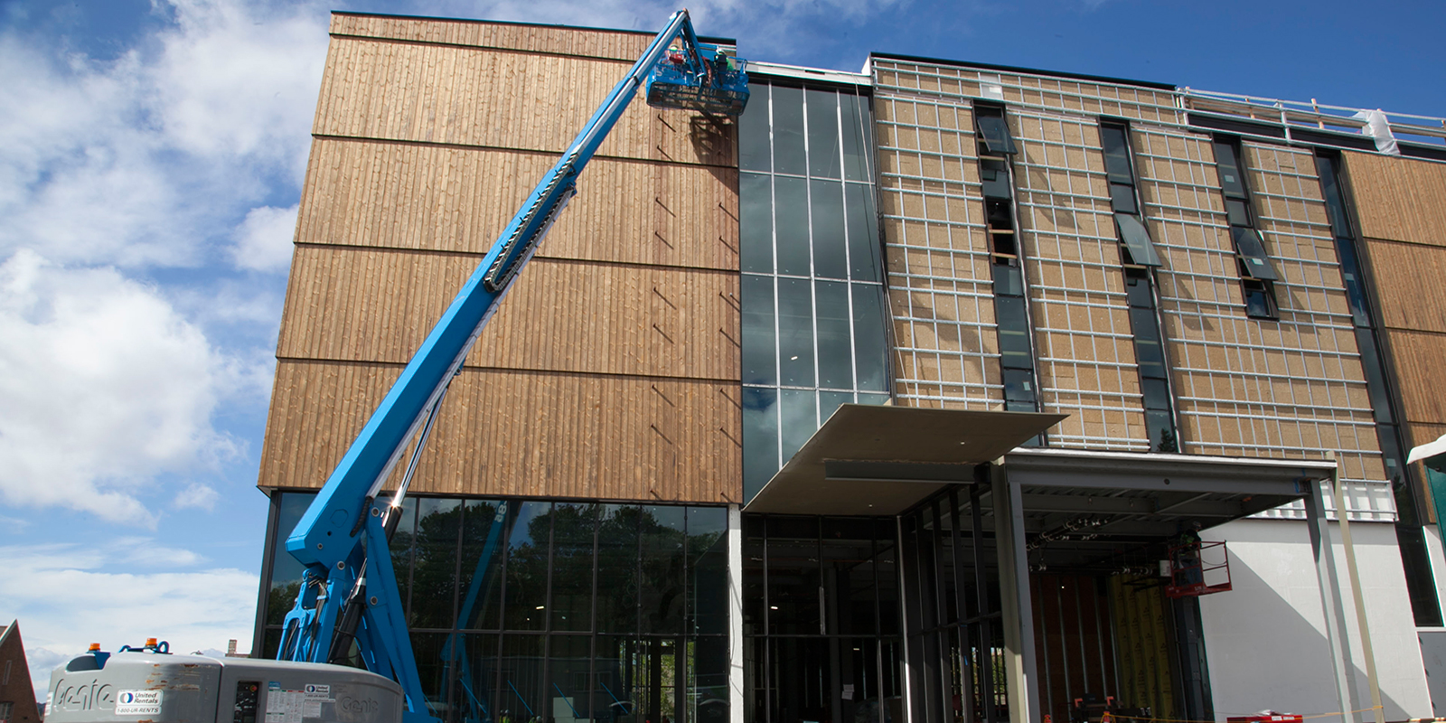 A crew member uses a lift to install siding on the New Burke exterior