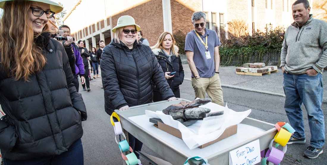 a team rolls the last object--a dinosaur fossil--on a cart as other staff cheer them on
