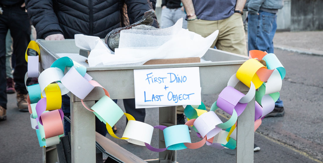 "close up of the cart holding the fossil with bunting and a handmade sign that says ""First Dino, Last Object"""