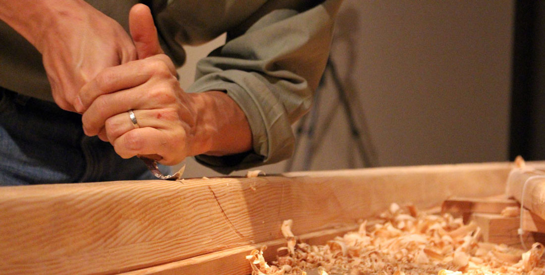 Hands using a hand tool to carve into the wood of a madrone tree