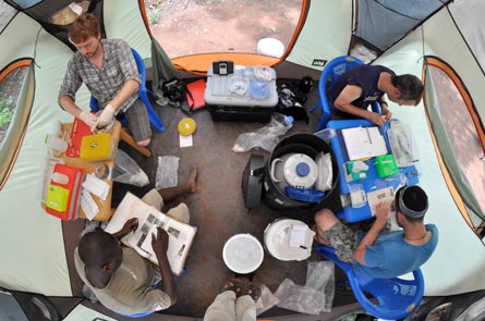 a group of researchers work in a field tent in Ghana