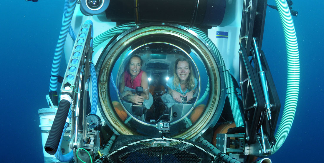 two women inside of a submarine port hole