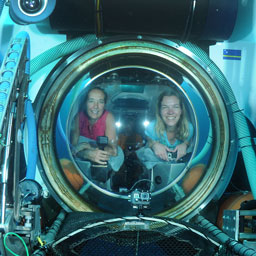 two women peer out of a porthole on a submersible underwater