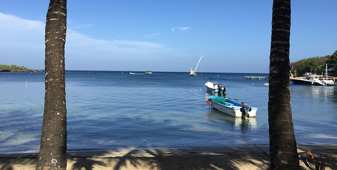 a beach with calm water and several boats anchored offshore