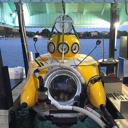 a yellow submersible on a dock over the water