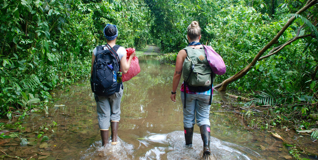 two women walk through heavy flooding while out in the field doing research