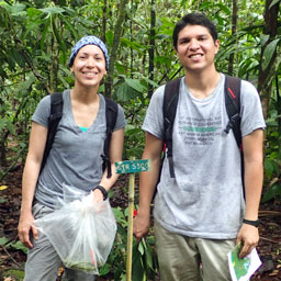 a woman and man stand in the jungle of south america while doing bat research
