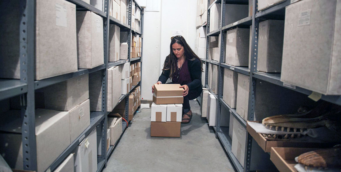 A woman researcher looks through boxes