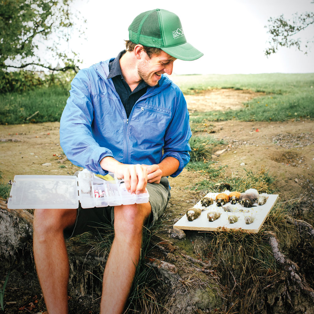 A male researcher in a green baseball cap prepares his tools for examining the birds he has collected