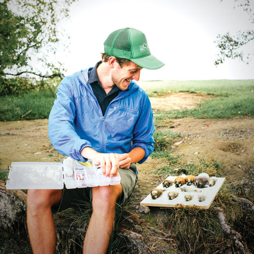 a young man sits with his field tools on his lap and bird specimens next to him