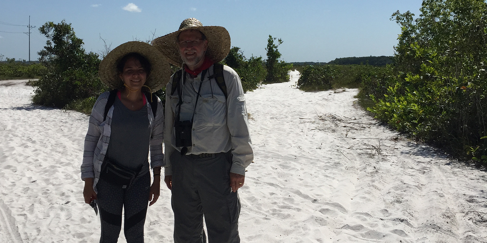 Two researchers posing outside surrounded by white sand that looks like snow