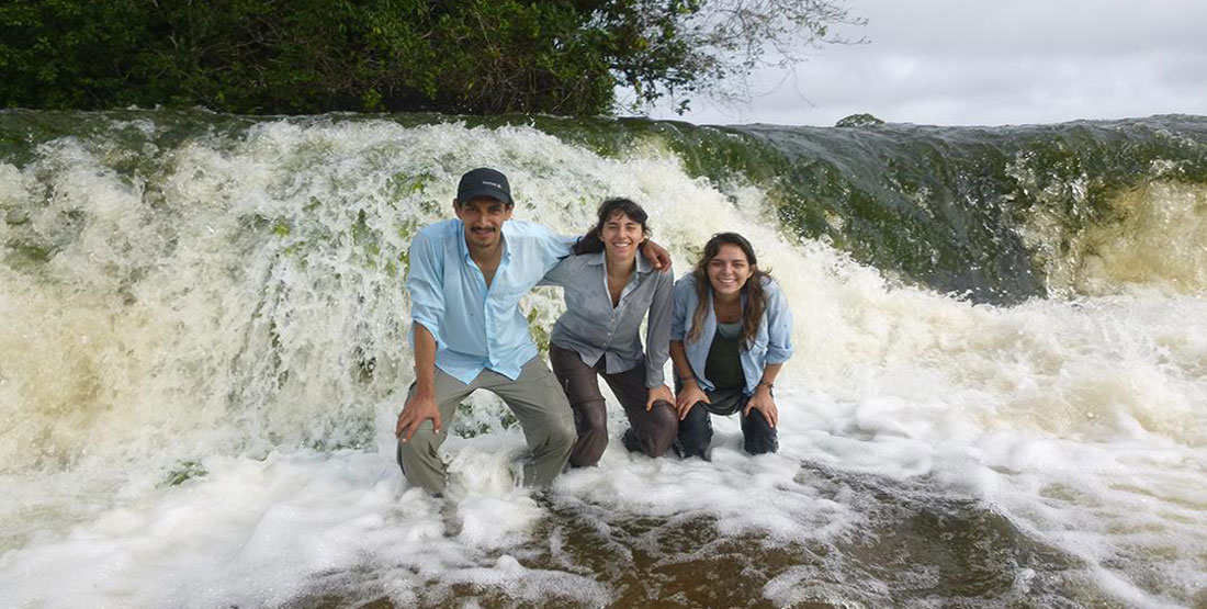 Three researchers stand in the river in the rapids