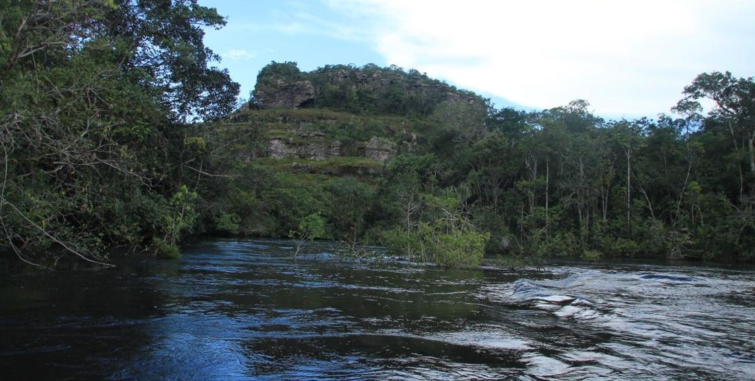 A river with vegitation on both sides and giant outcrop of rock