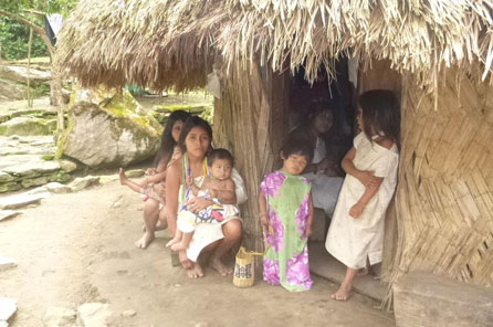 A family in front of a simple house with a thatched roof
