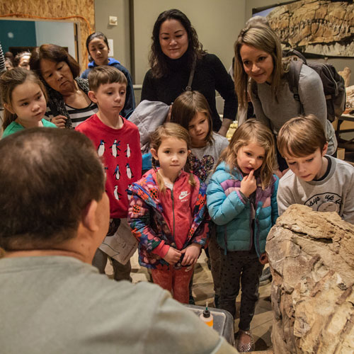 a group of kids and two women watch as fossils are prepared