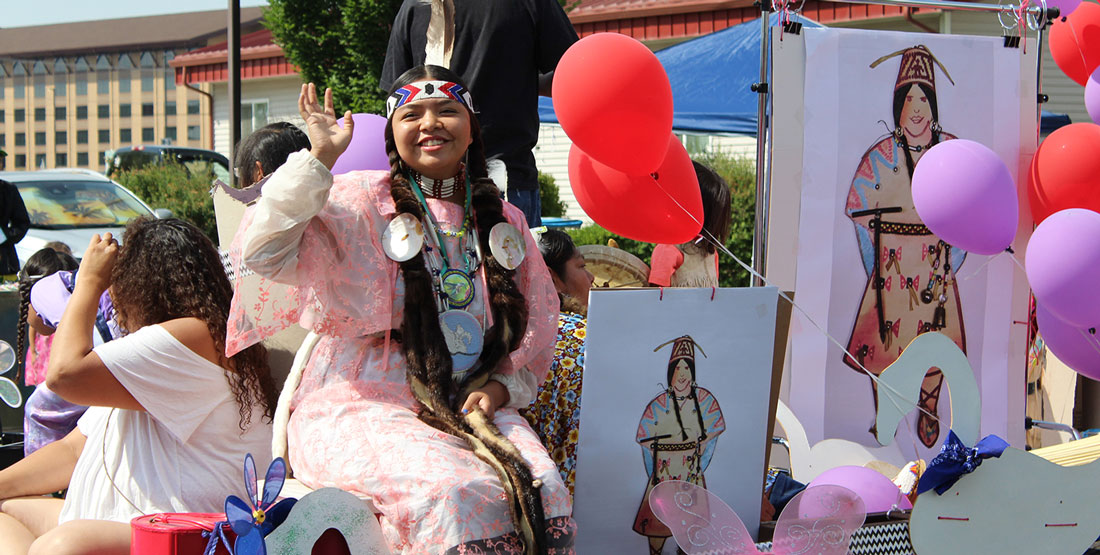 a teenage girl wearing traditional Yakama Nation attire waves from a parade float