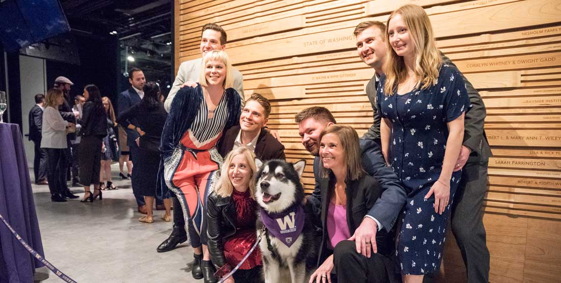 group of people pose with Dubs the Husky