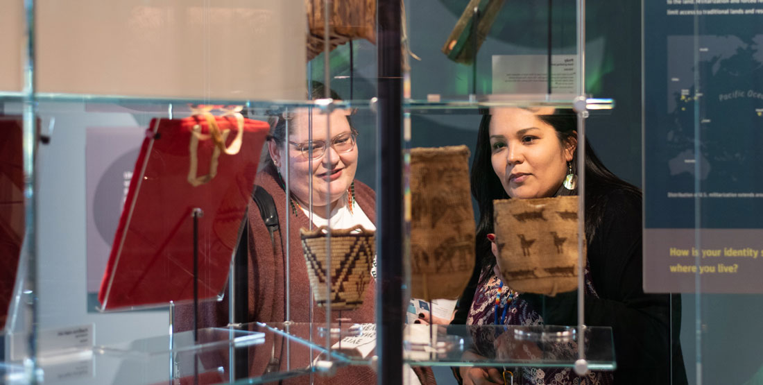 Two women look at a basketry item on glass shelving