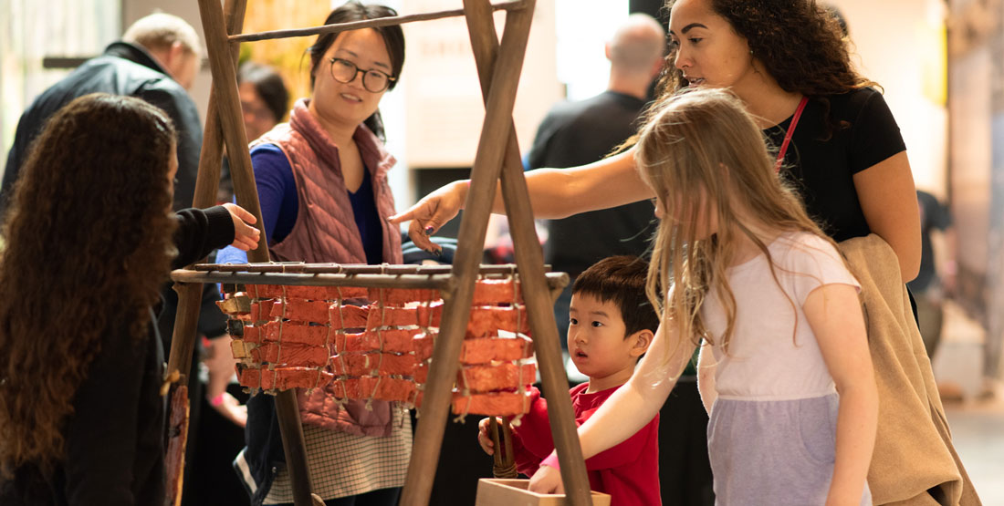 families touch an interactive exhibit depicting a salmon cooking over a fire pit