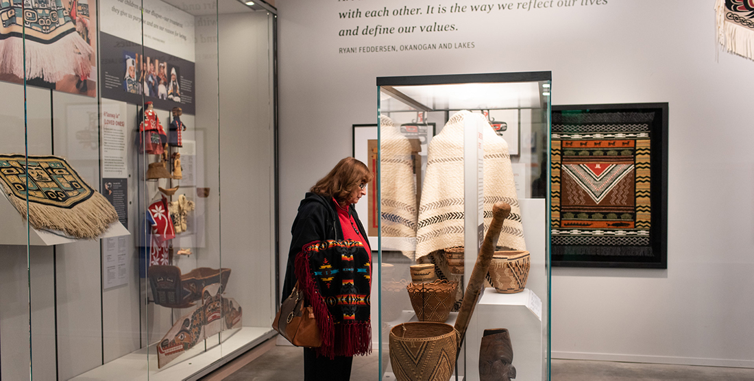 a woman looks into a case with Native American objects in it