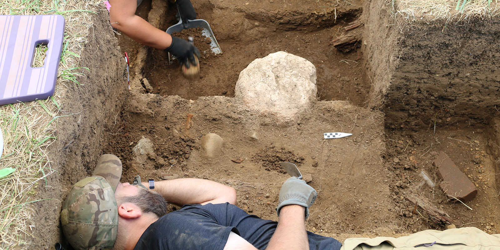 A man digs in a pit with rock artifacts around him