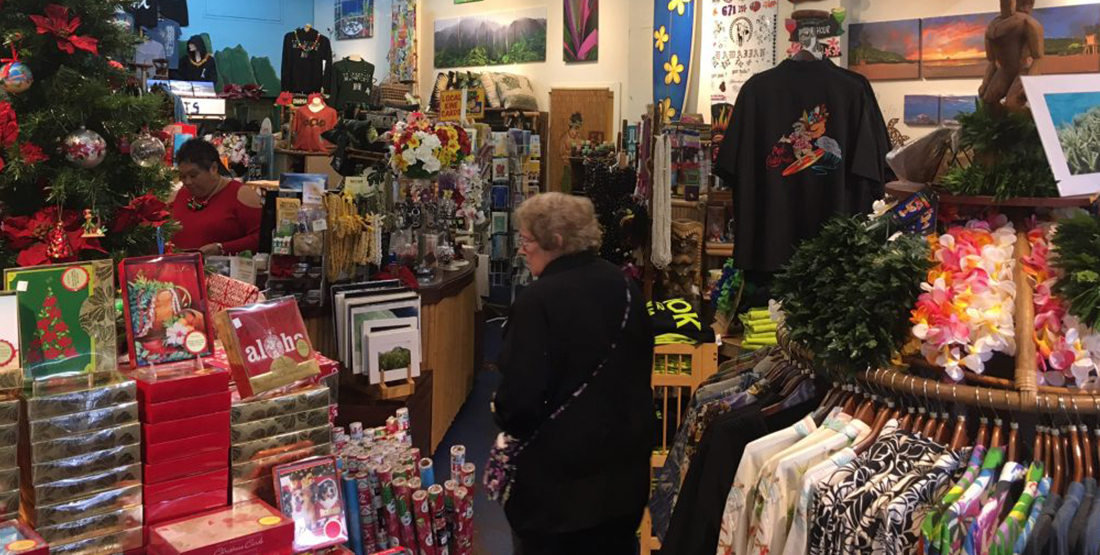 A woman shops in a store filled with cards, gift wrap and shirts