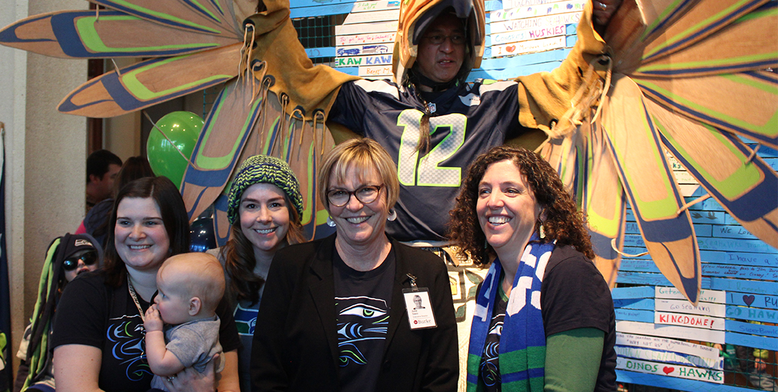 A group of women with a man dressed in wooden Seahawks regalia