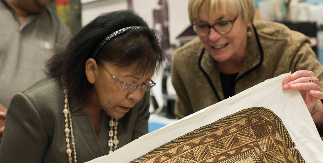 Two women look at a woven textile