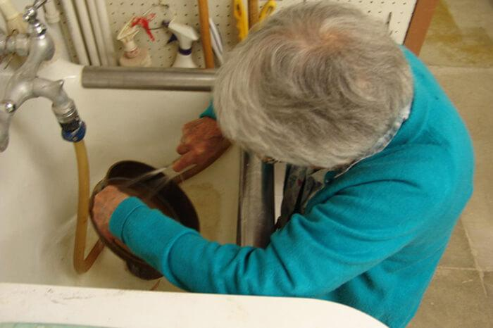 a woman rinses sediment in a sink