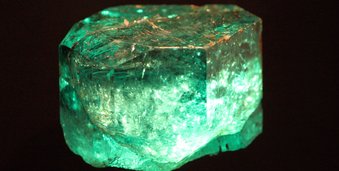 A close up view of an emerald that appears to be glowing