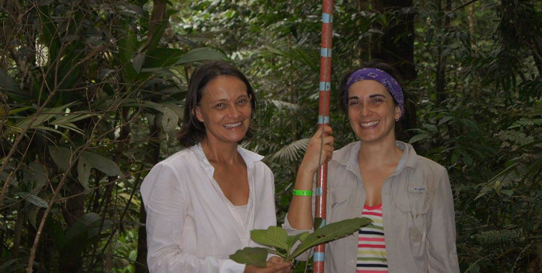 two woman hold a tall pole and leaves while doing fieldwork