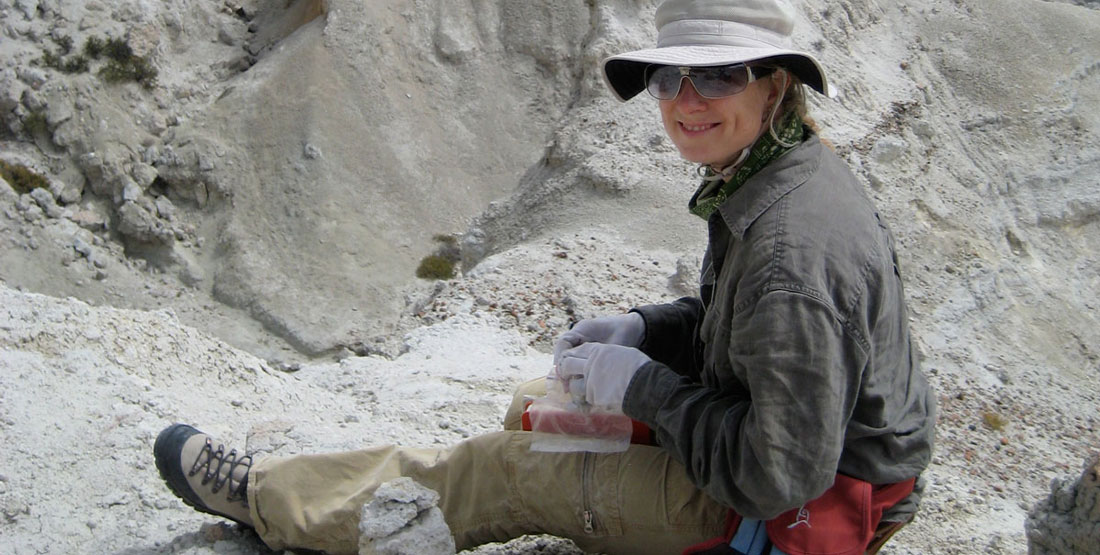 A female researcher wearing a hat and sunglasses sits on the rocky ground