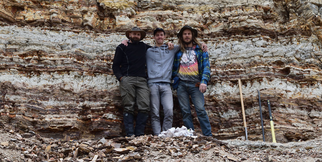 three young men stand in front of a rock wall showing many stratigraphic layers
