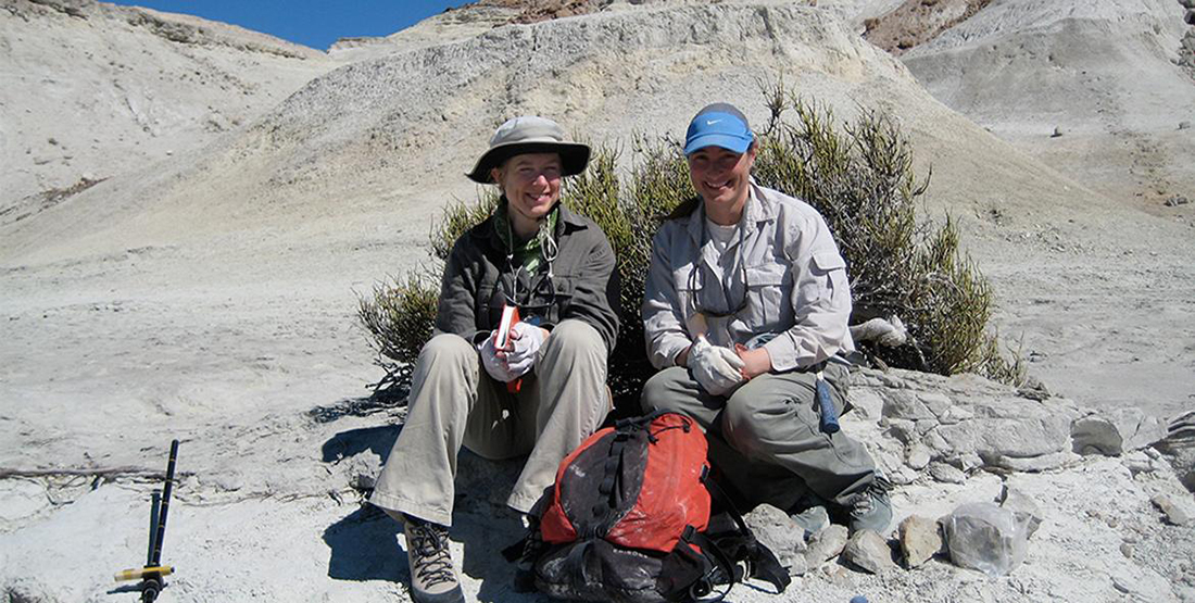 Two researchers sit with their backpacks in the desert