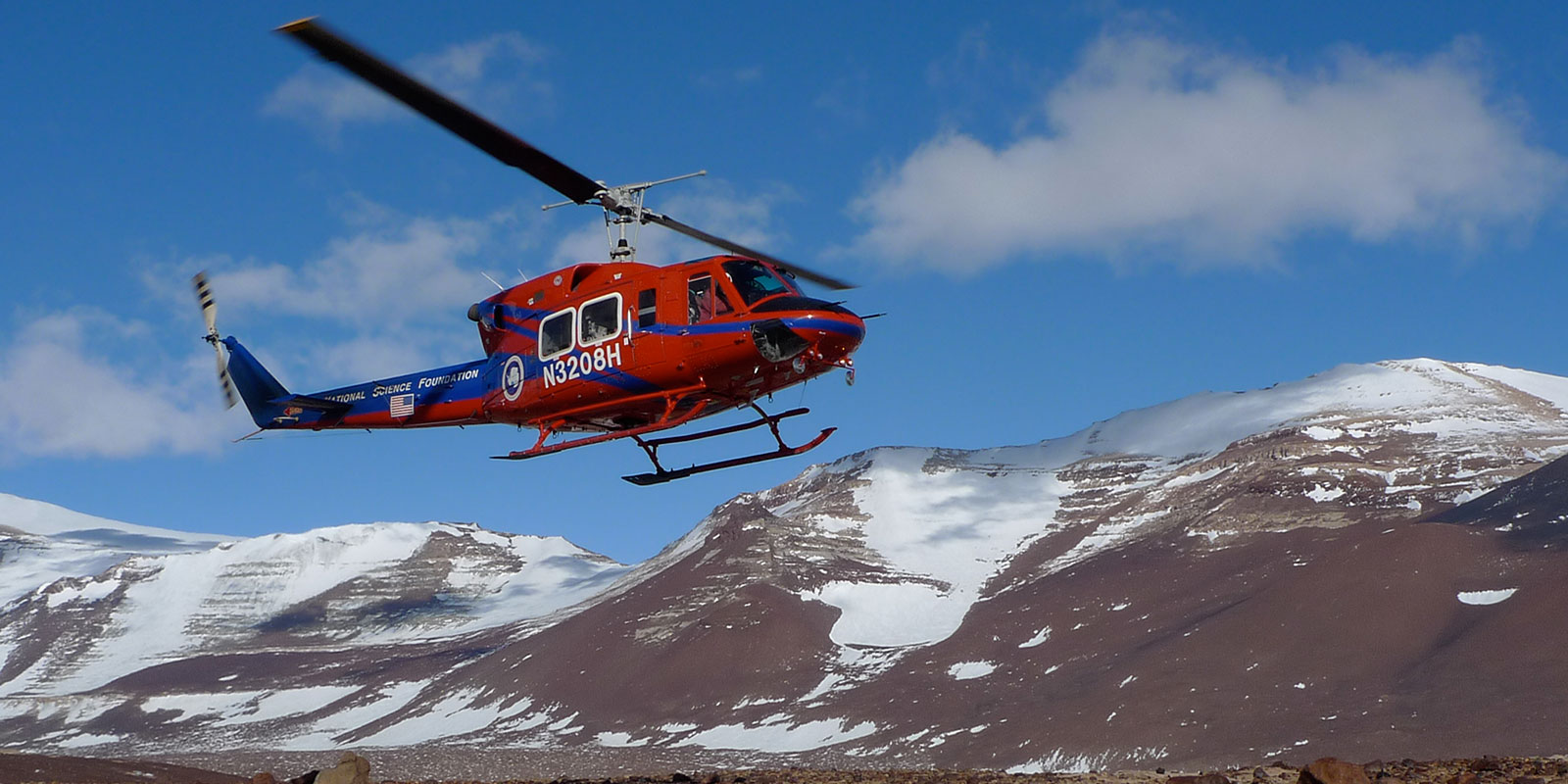 A helicopter takes off with the barren Antarctic skyline in the background
