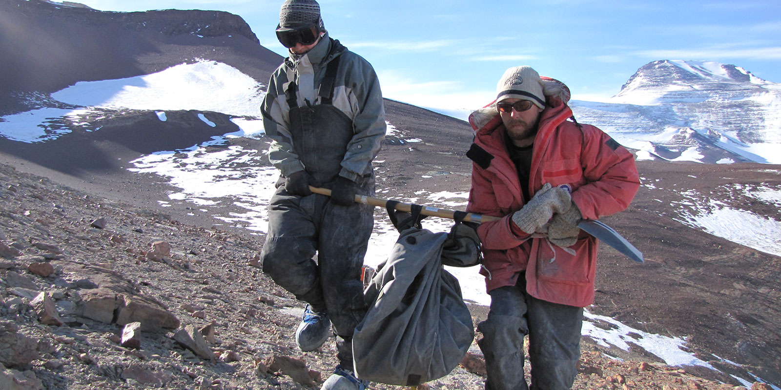 Two men use a shovel to carry a heavy fossil encased in rock out of the Antarctic landscape
