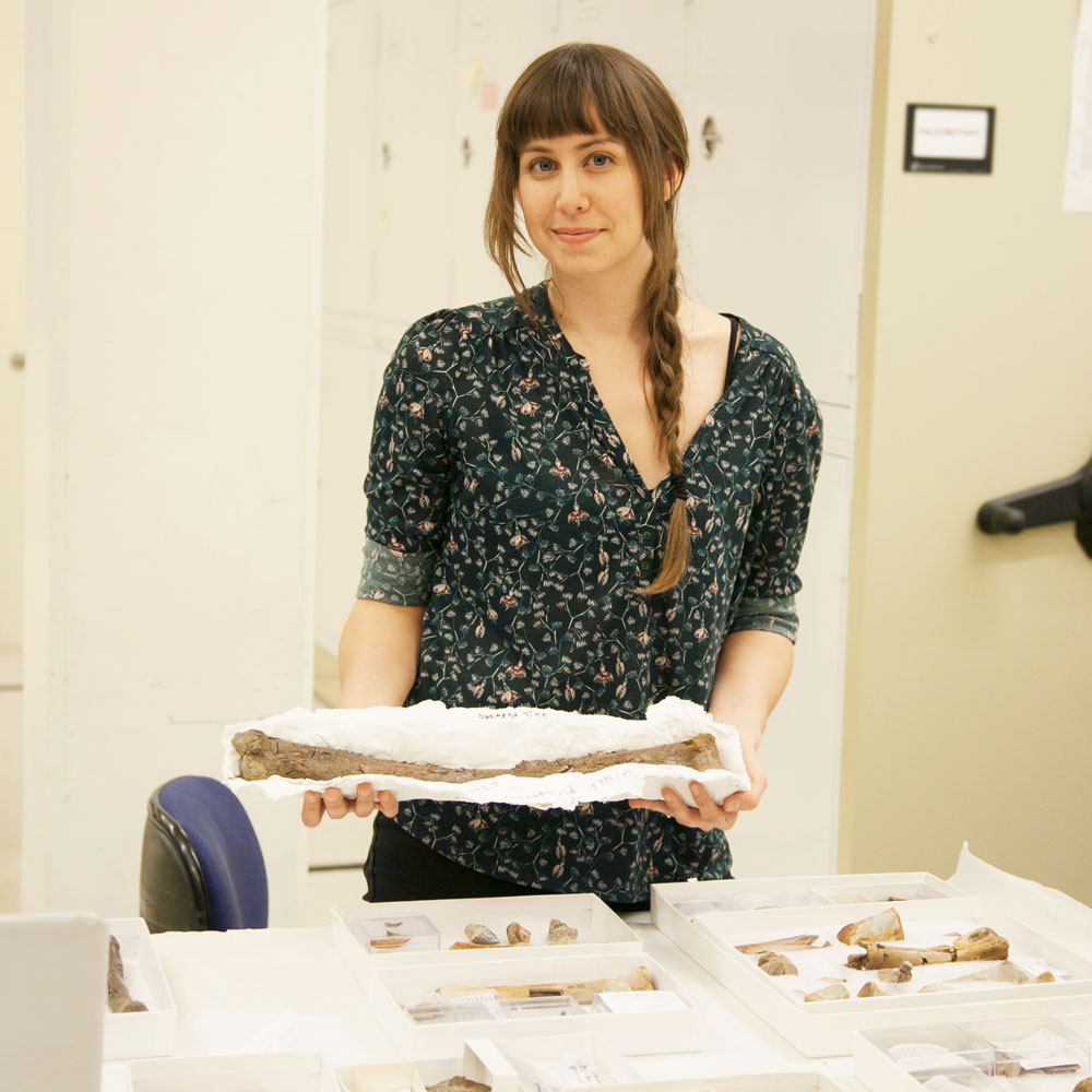 a young woman stands in front of a table full of fossils while holding a large fossil