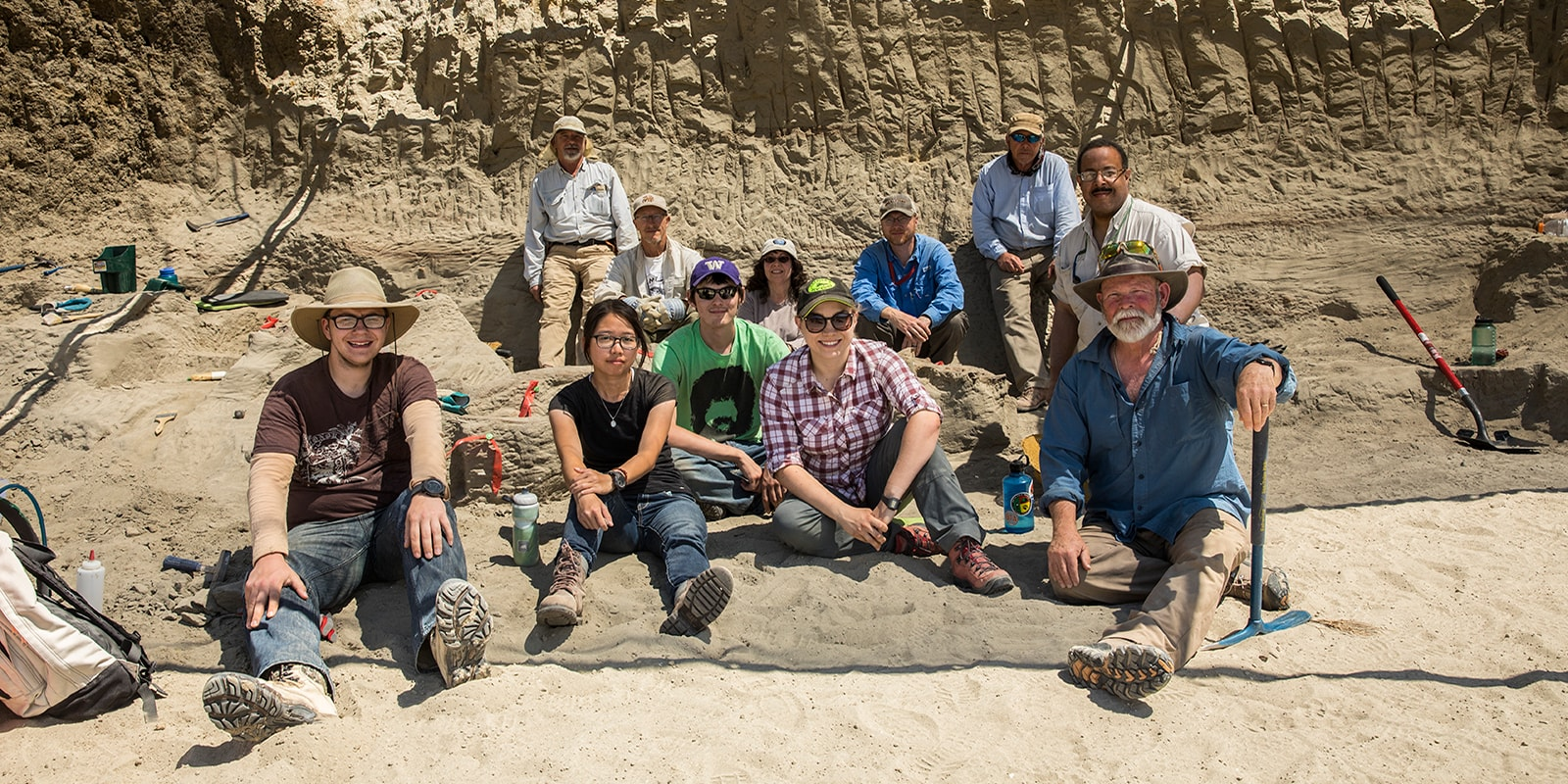 A group of eleven people posing for a group photo at a t.rex dig site