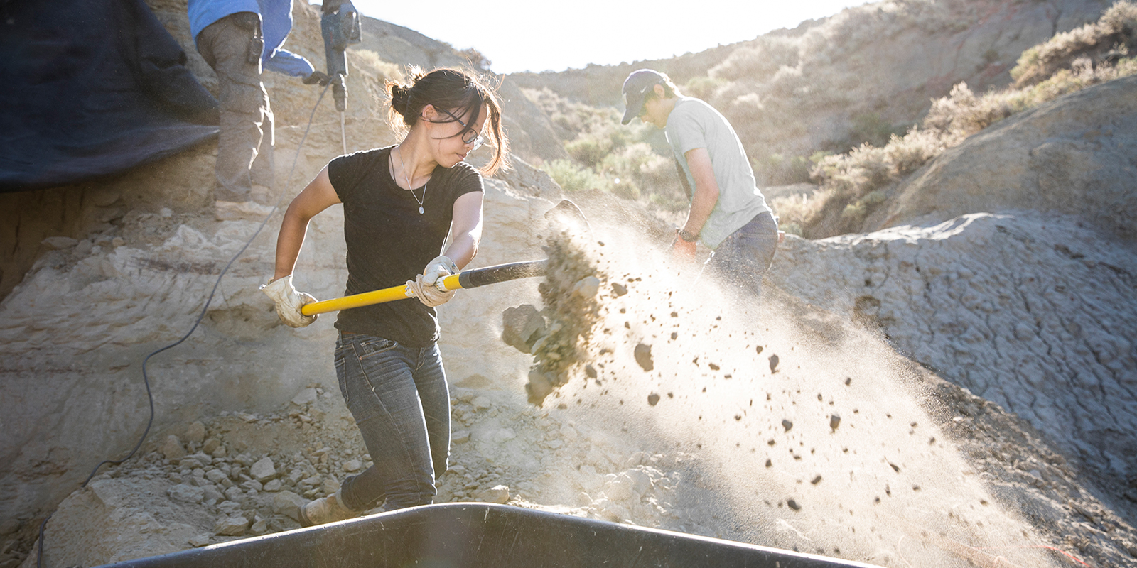 A woman shoveling dirt within a paleontology dig
