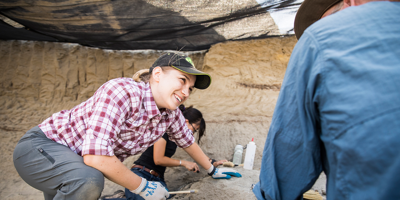 A woman in dirty working clothes smiling at another person under a canopy on a paleontology dig