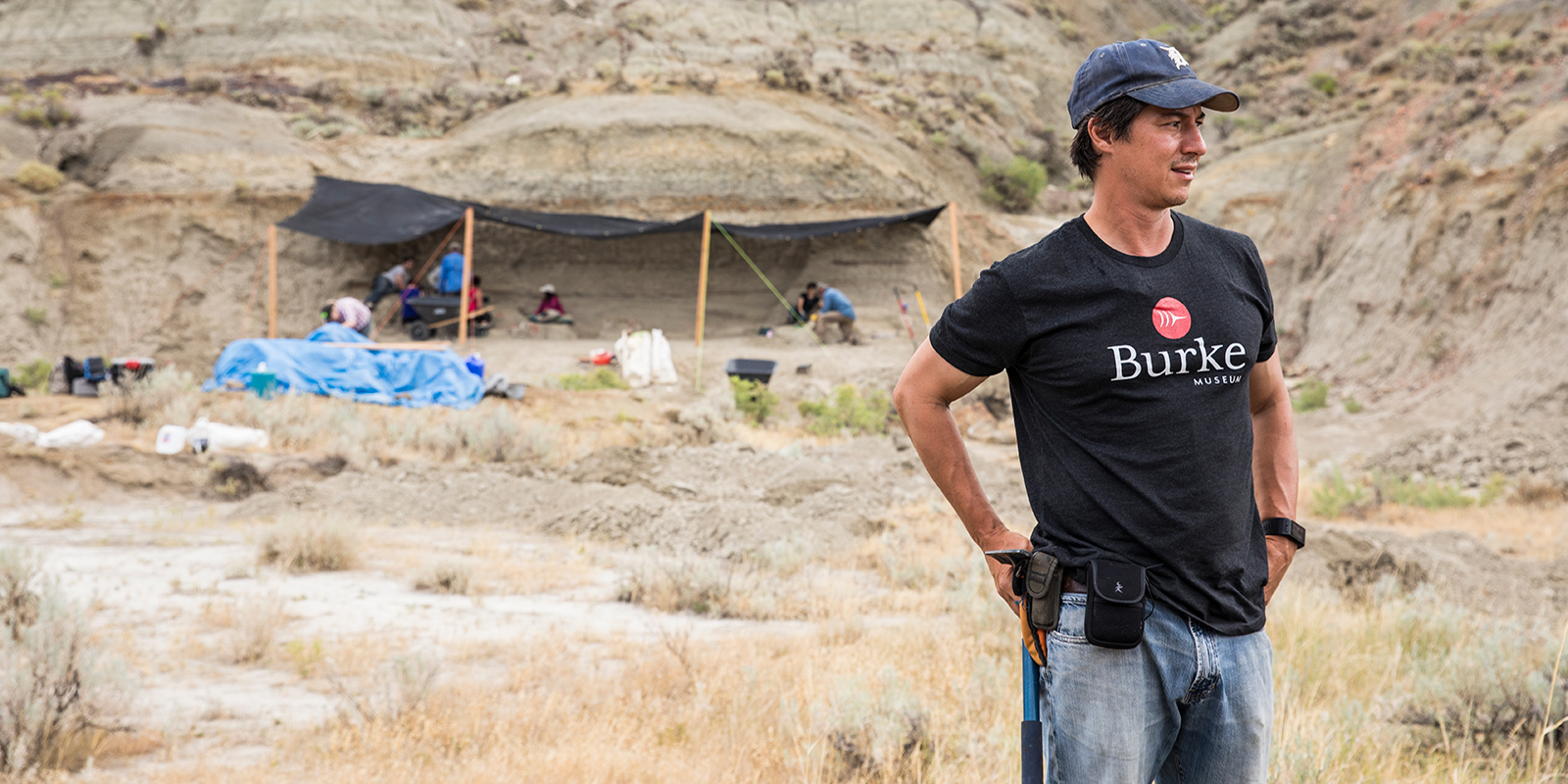 A palentologist with a Burke Museum tee shirt standing in front of a paleontology dig site