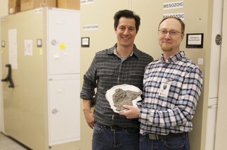 Two men stand amongst museum collections compactors and hold a small fossil