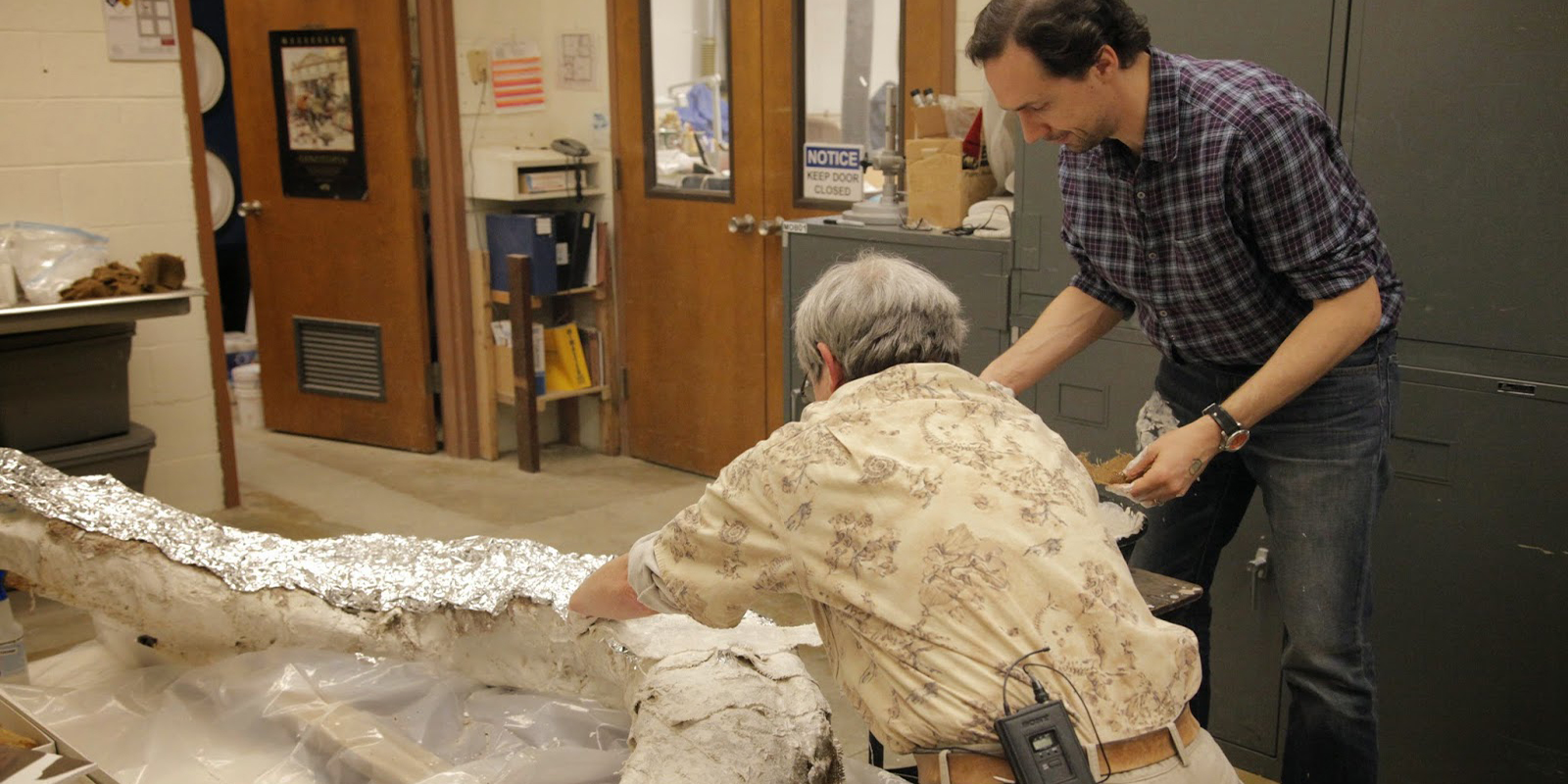 Two researchers cover the mammoth tusk in plaster