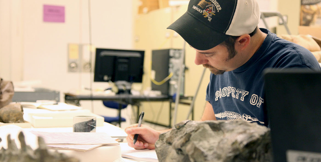 a young man writes in a field notebook while studying fossils in the Burke collection