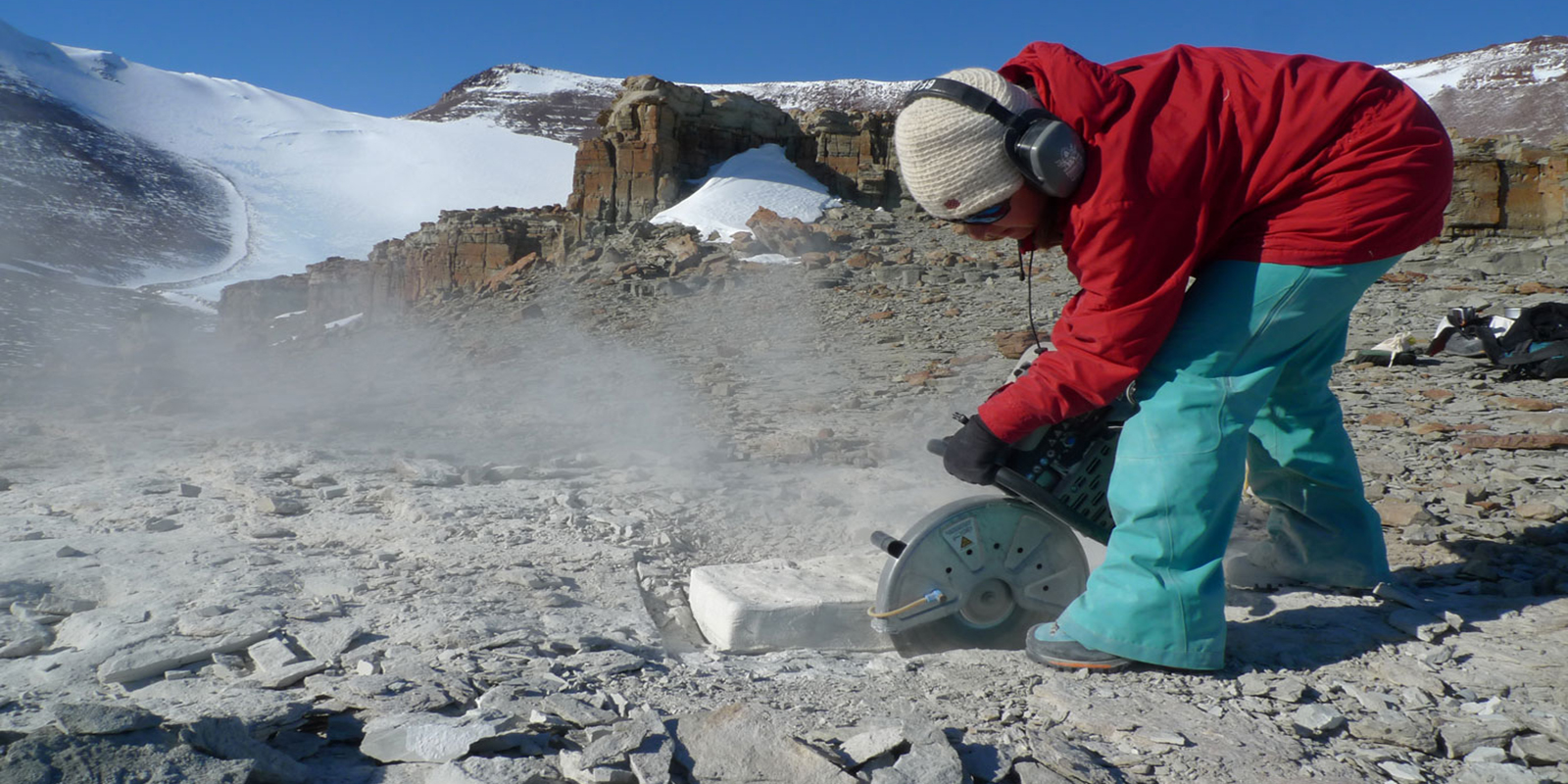 A young woman uses a rock saw to cut a pedestal around on fossil