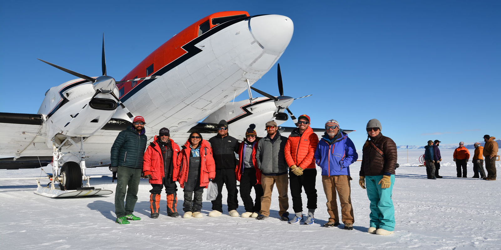 group of scientists stand in front of the airplane that dropped them off on the snow-covered runway in Antarctica