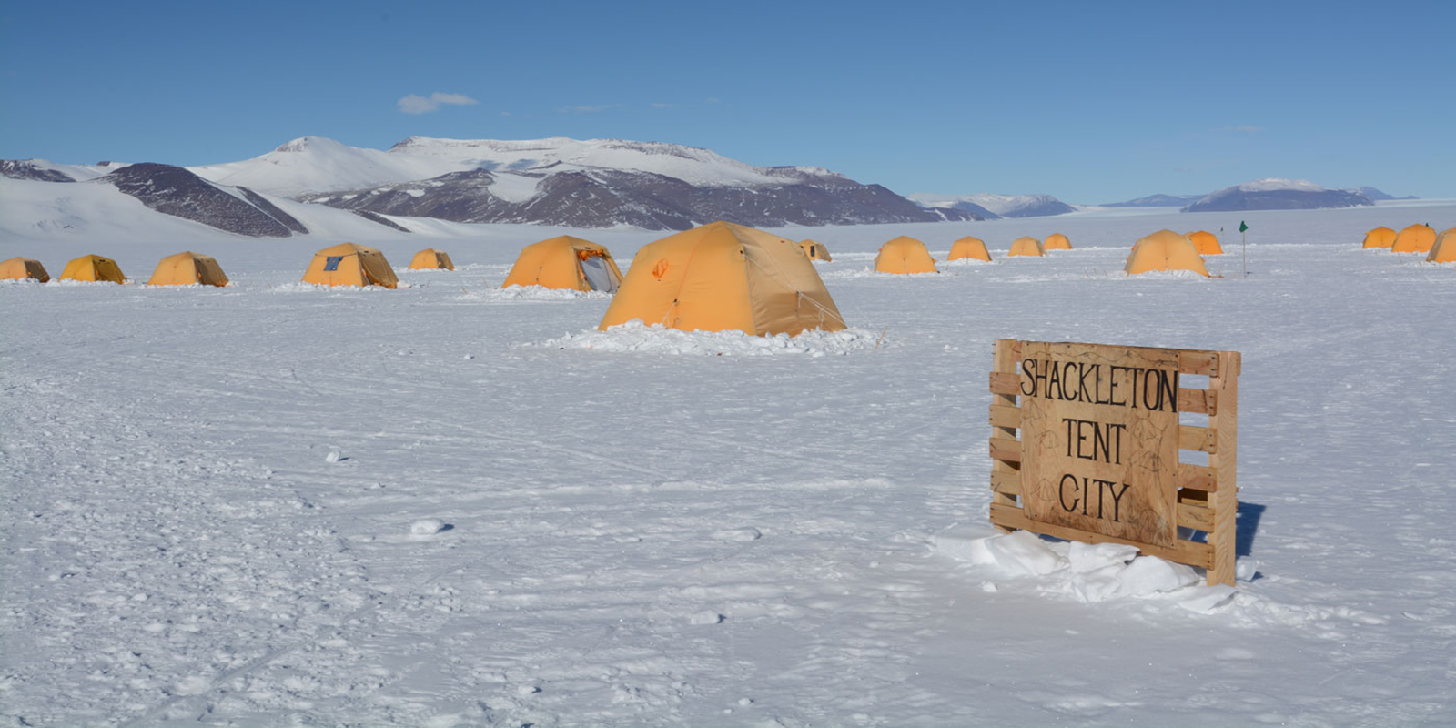 yellow tents sporadically placed on the snow form a camp